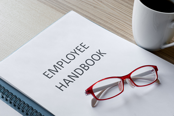 Employee handbook with glasses and coffee on desk